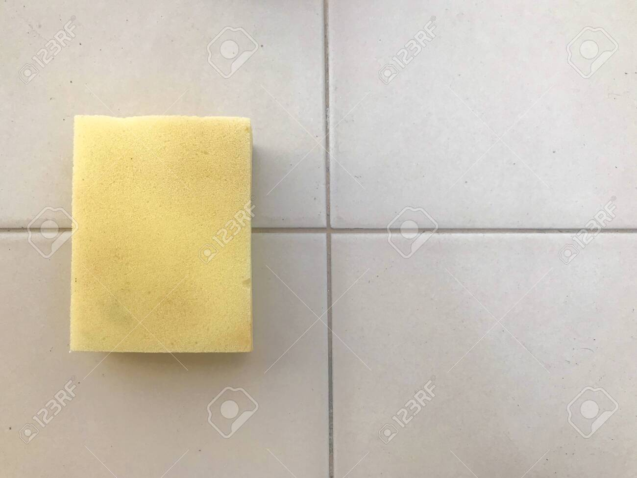 yellow sponge for wash cleaning on ceramic tile wall background. - 123104643