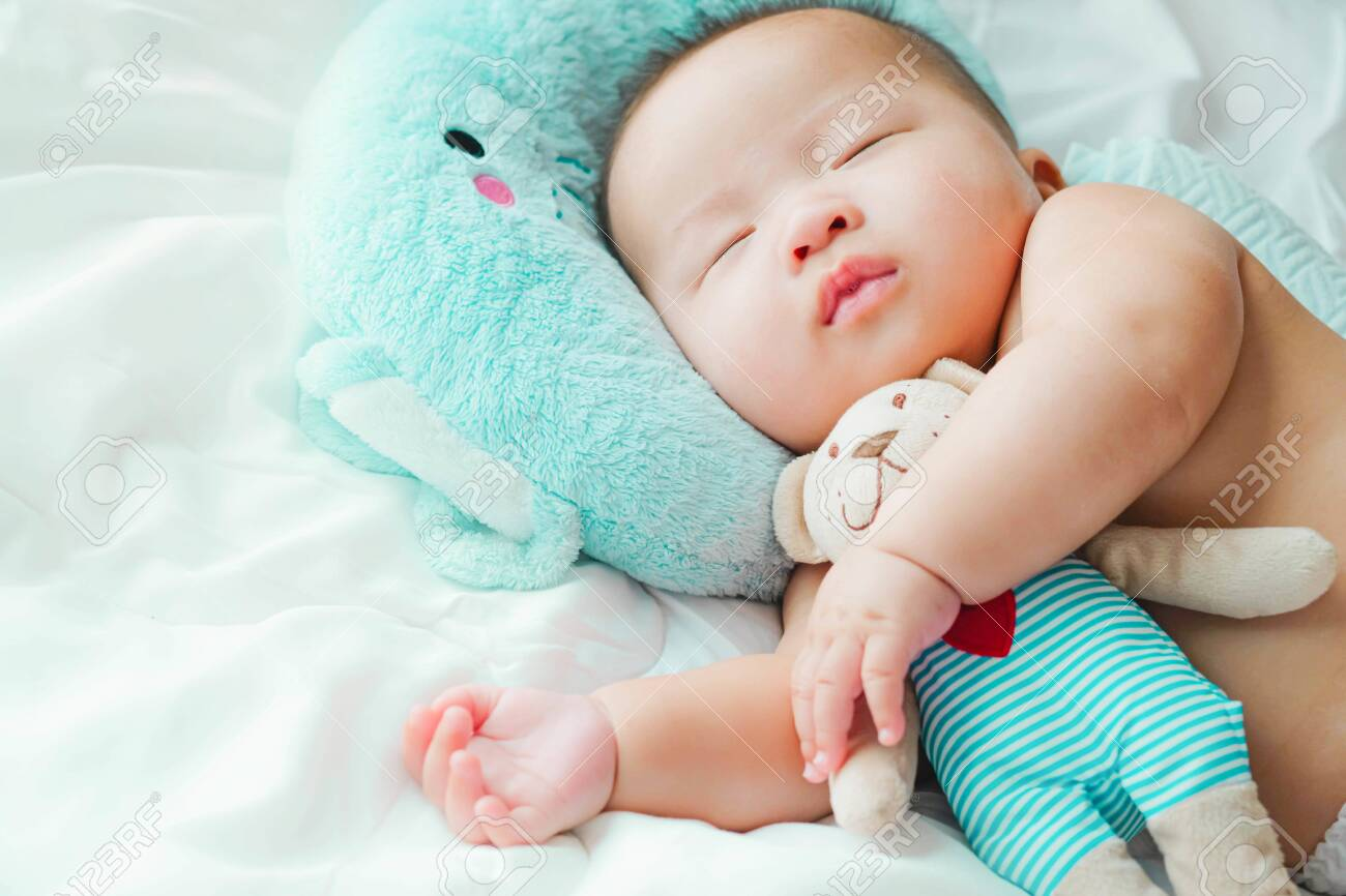 Portrait of a newborn Asian baby on the bed, A child resting on a bed sleeping - 141433087
