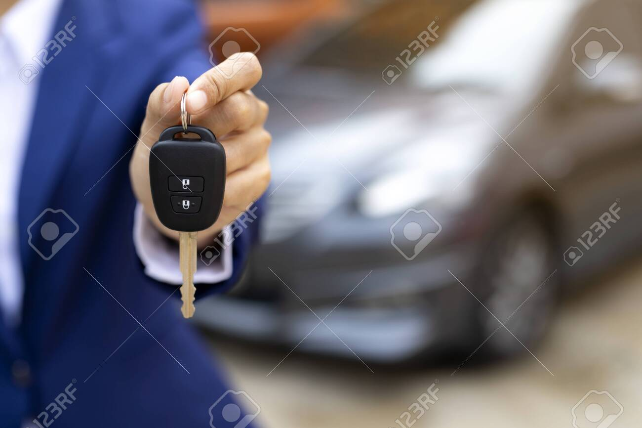 Close up of dealer giving key to new owner and shaking hands in auto show.auto business, car sale, deal,concept - 146080635