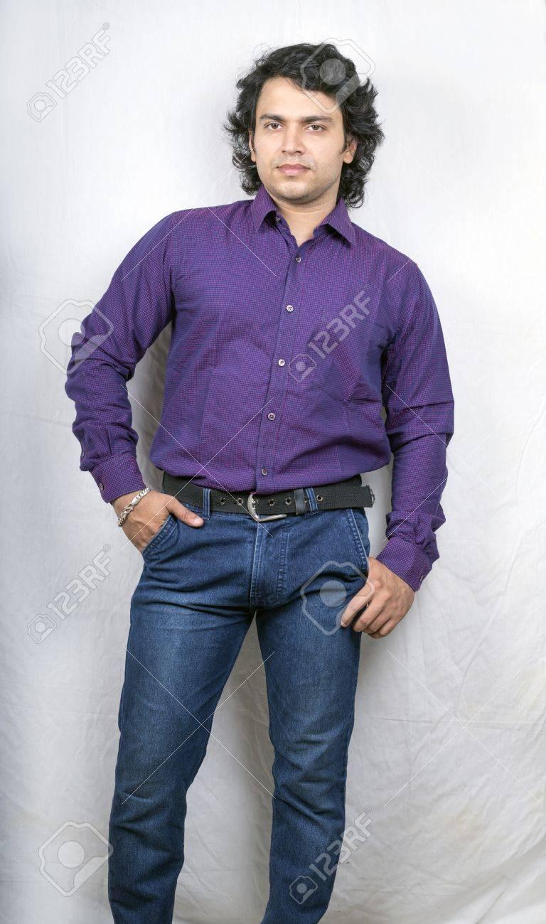 6e85d96c0a Foto de archivo - Modelo masculino indio en camisa púrpura y pantalones  vaqueros azules