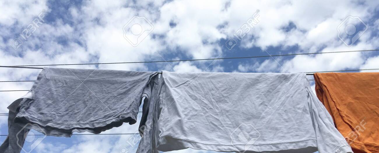 clothes hanging after washing. shirts to dry on a cloudy sky background. - 148577129