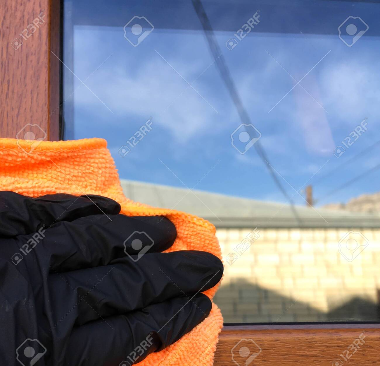 Window cleaning with detergent, spring cleaning concept.Hand in a black glove with a special tool washes a soap window on a background of trees - 148013015