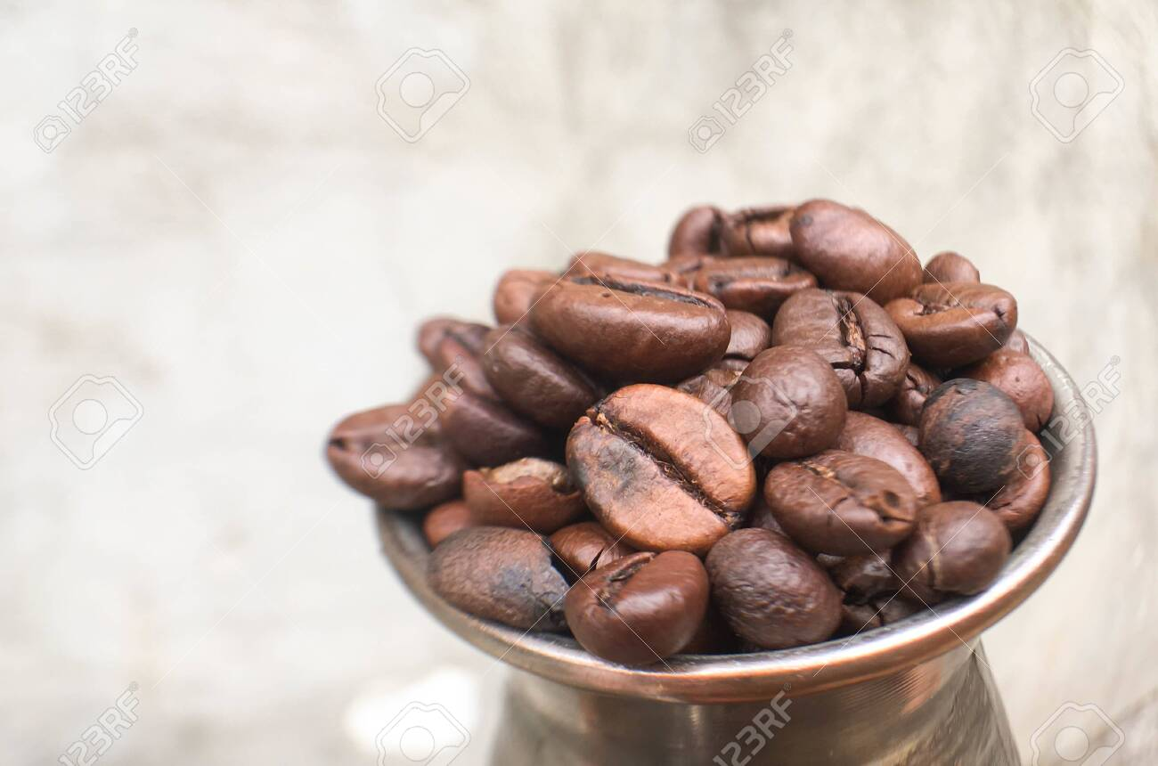 a pile of coffee beans in turk and on the table. Coffee texture and background image. - 147704099