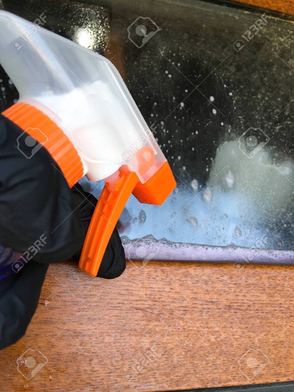 A woman in a black glove cleans a window with a spray bottle. House cleaning. Washing dirty window detergents in summer. - 149039771