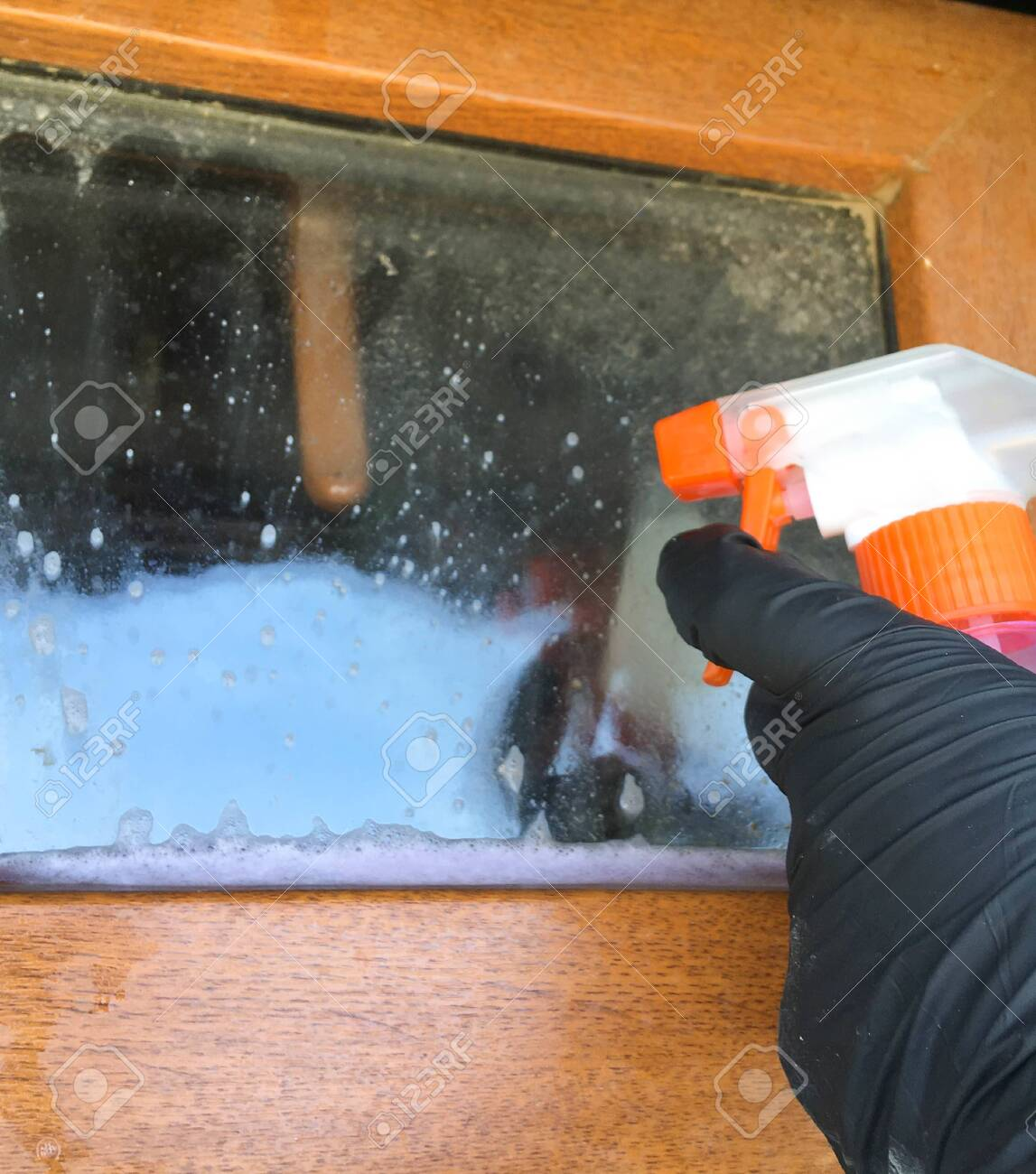 A woman in a black glove cleans a window with a spray bottle. House cleaning. Washing dirty window detergents in summer. - 149039779