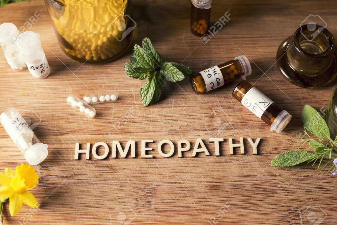 Table with written text Homeopathy, homeopathy globules and bottles - 53419231