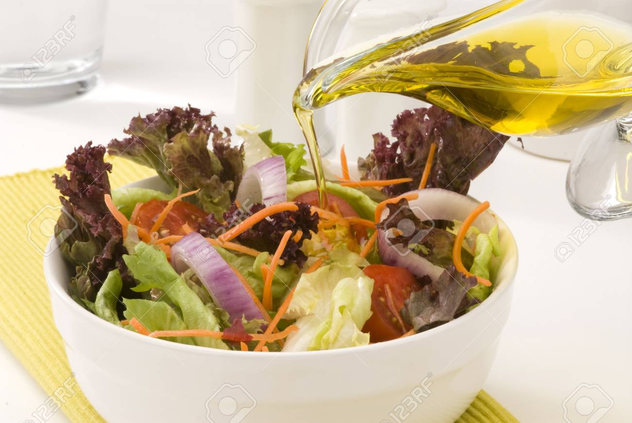 Olive oil pouring into a fresh summer salad. Selective focus. Stock Photo - 15538329