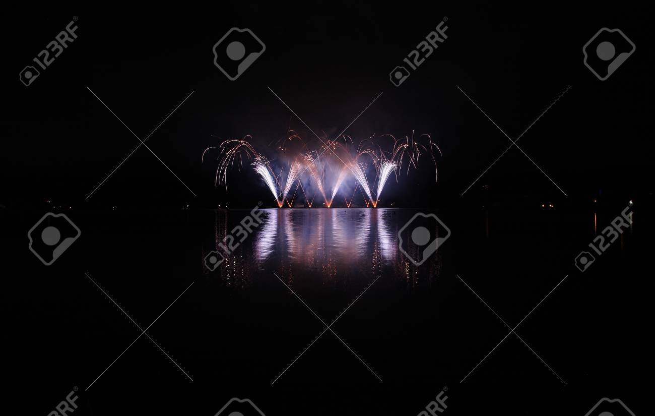 Colorful fireworks with reflection on lake and night sky in background. - 42004311