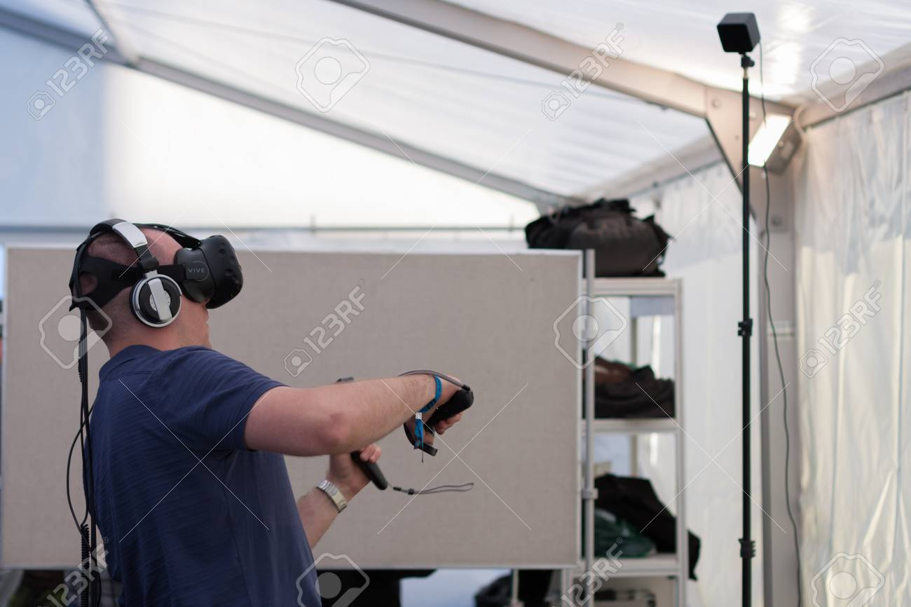 BRNO, CZECH REPUBLIC - APRIL 30, 2016: Young man with VR - glasses and controllers plays game at Animefest, anime convention on April 30, 2016 Brno, Czech Republic - 58008622