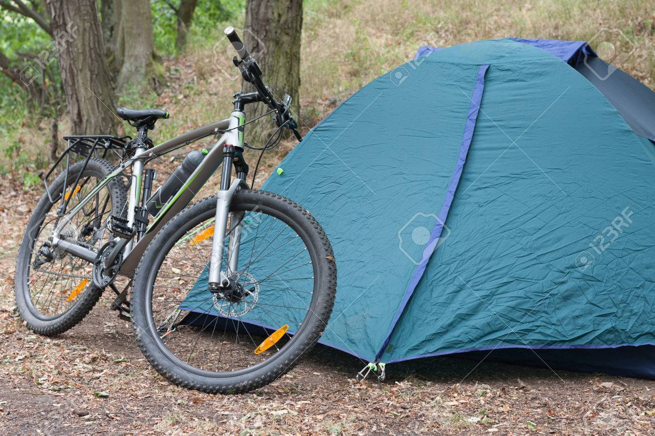 Mountain bike in front of closed tent in the woods in the summer morning Stock Photo & Mountain Bike In Front Of Closed Tent In The Woods In The Summer ...