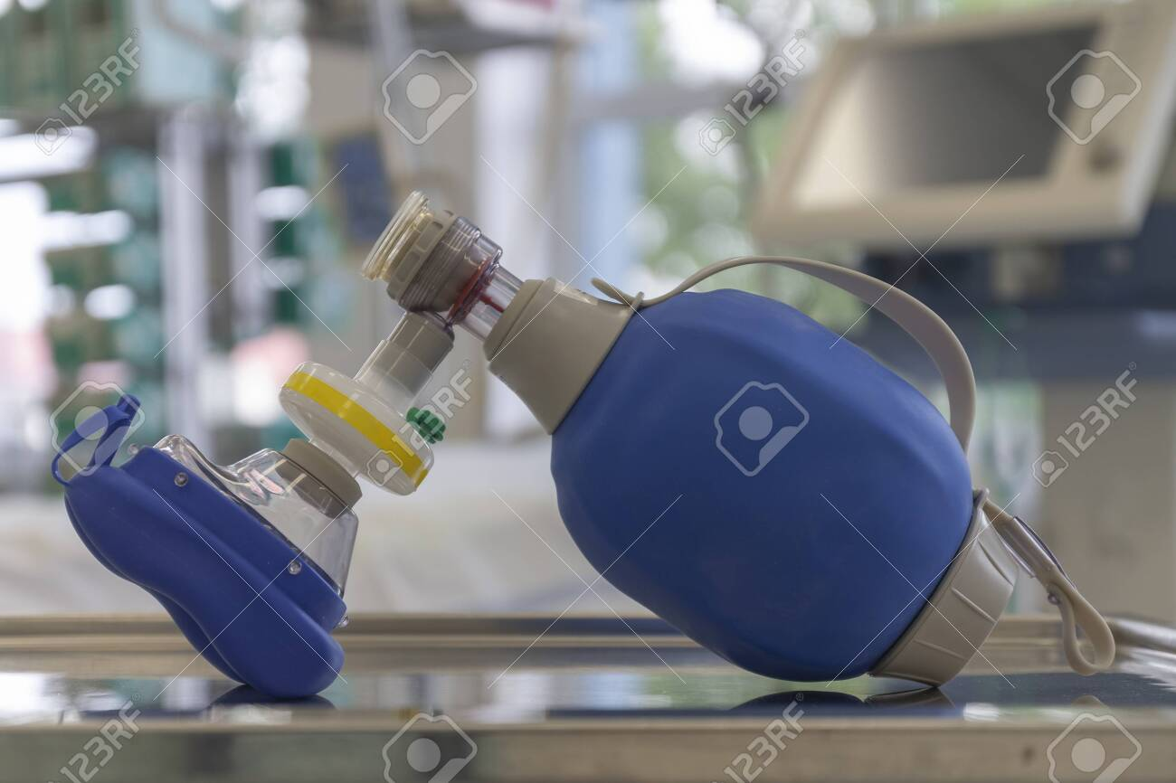 Breathing bag with filter and mask , on background medical ventilator in ICU in hospital, a place where can be treated patients with pneumonia caused by coronavirus covid-19. - 144260096