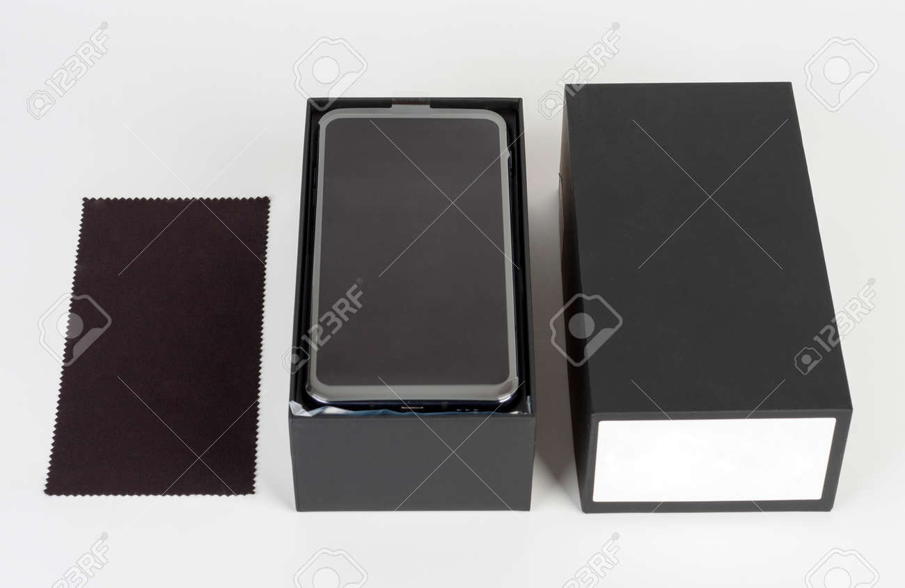 Unboxing of touchscreen smartphone, paper box and clean cloth. Studio shoot on white background. - 162659767