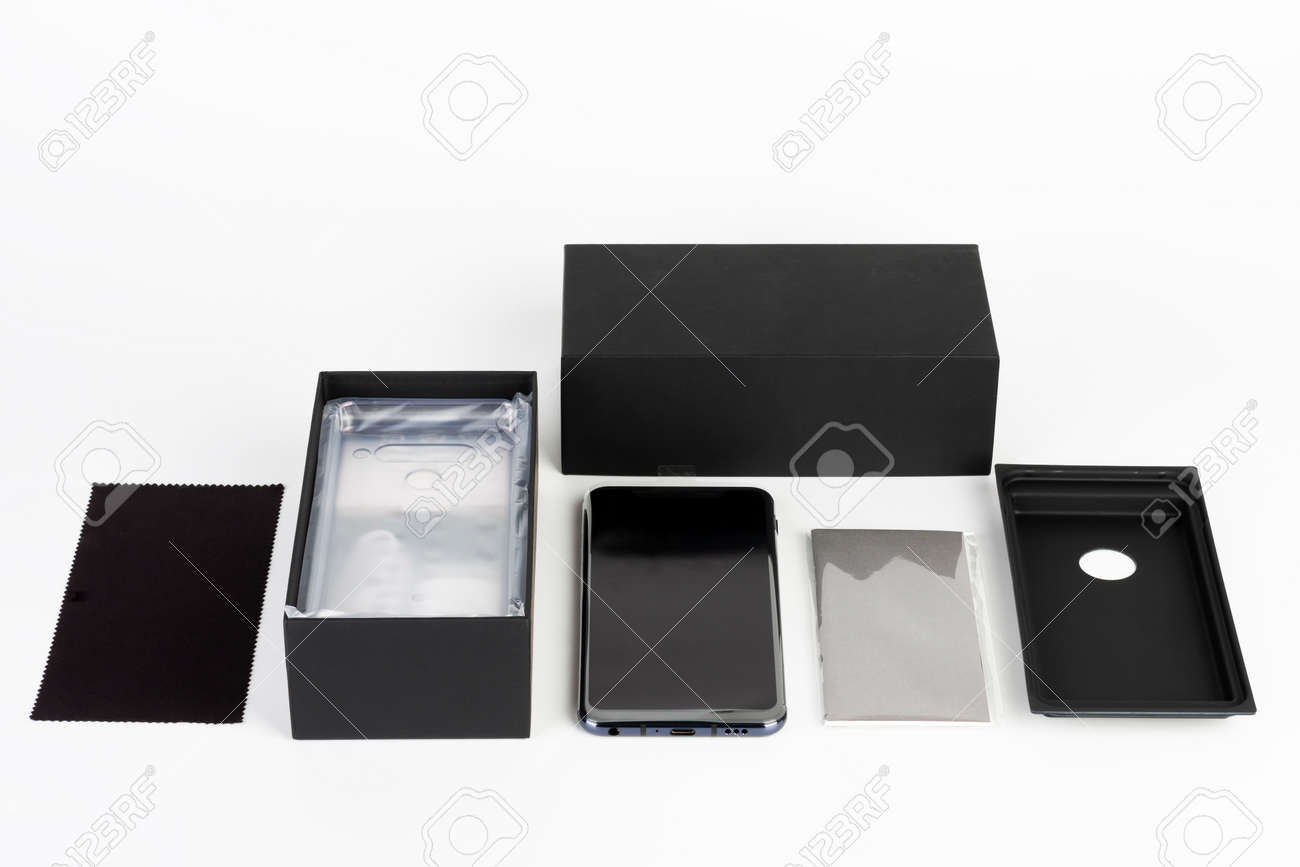 Unboxing of touchscreen smartphone, paper box and clean cloth. Studio shoot on white background. - 162659770