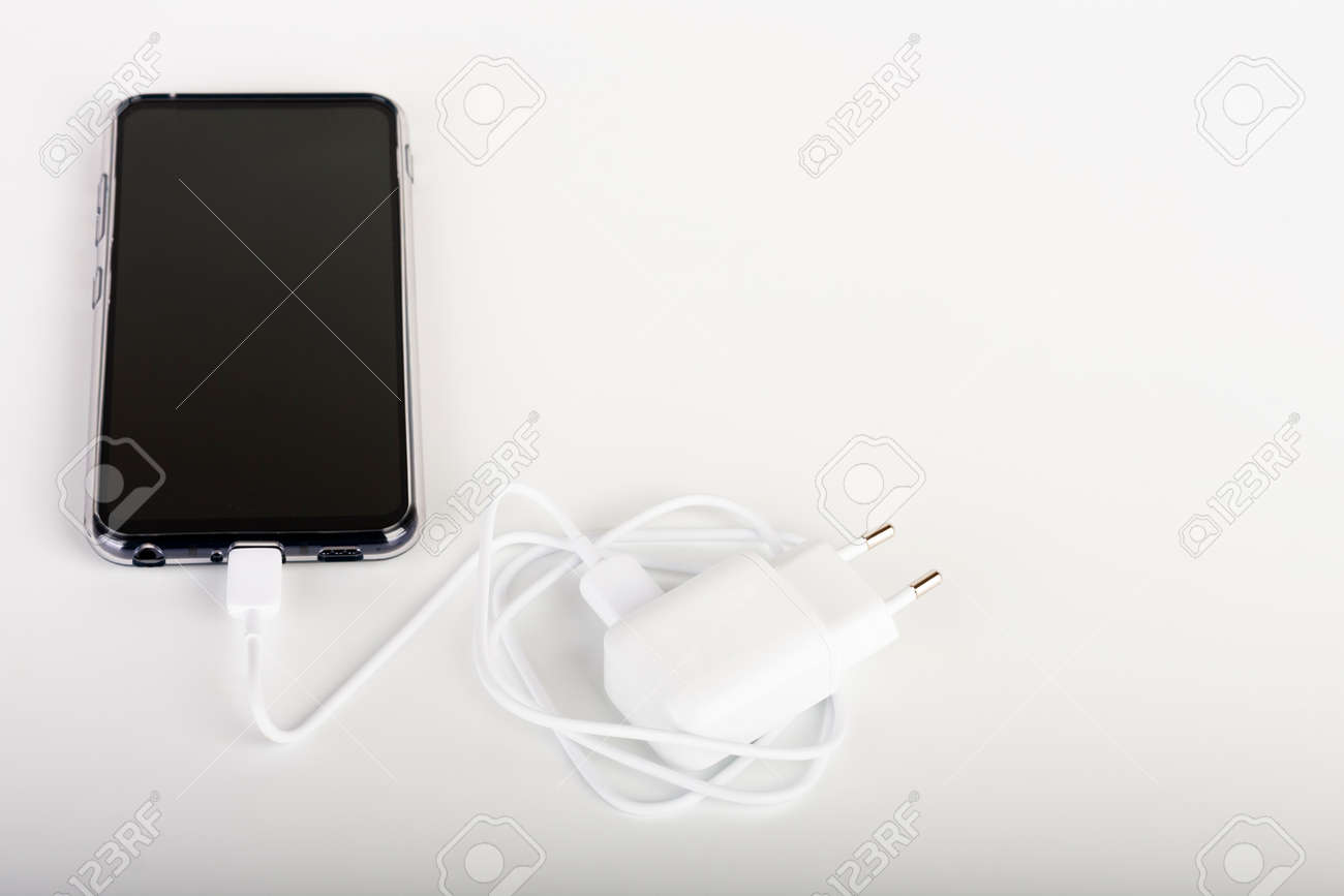 Touchscreen smartphone and white charger and white cable for charging in white background. - 162659586