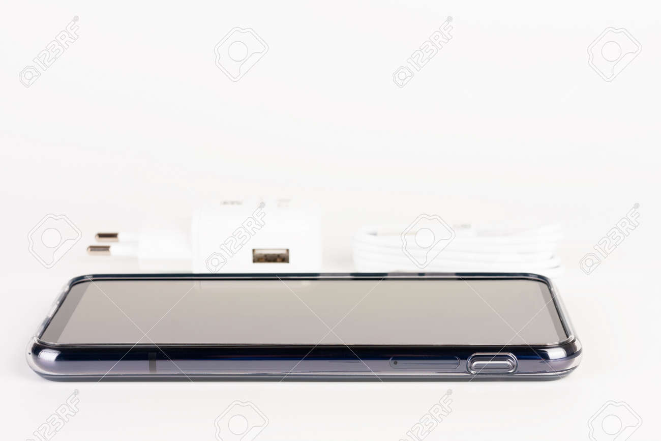 Touchscreen smartphone in silicone cover, charger in background. - 162659598