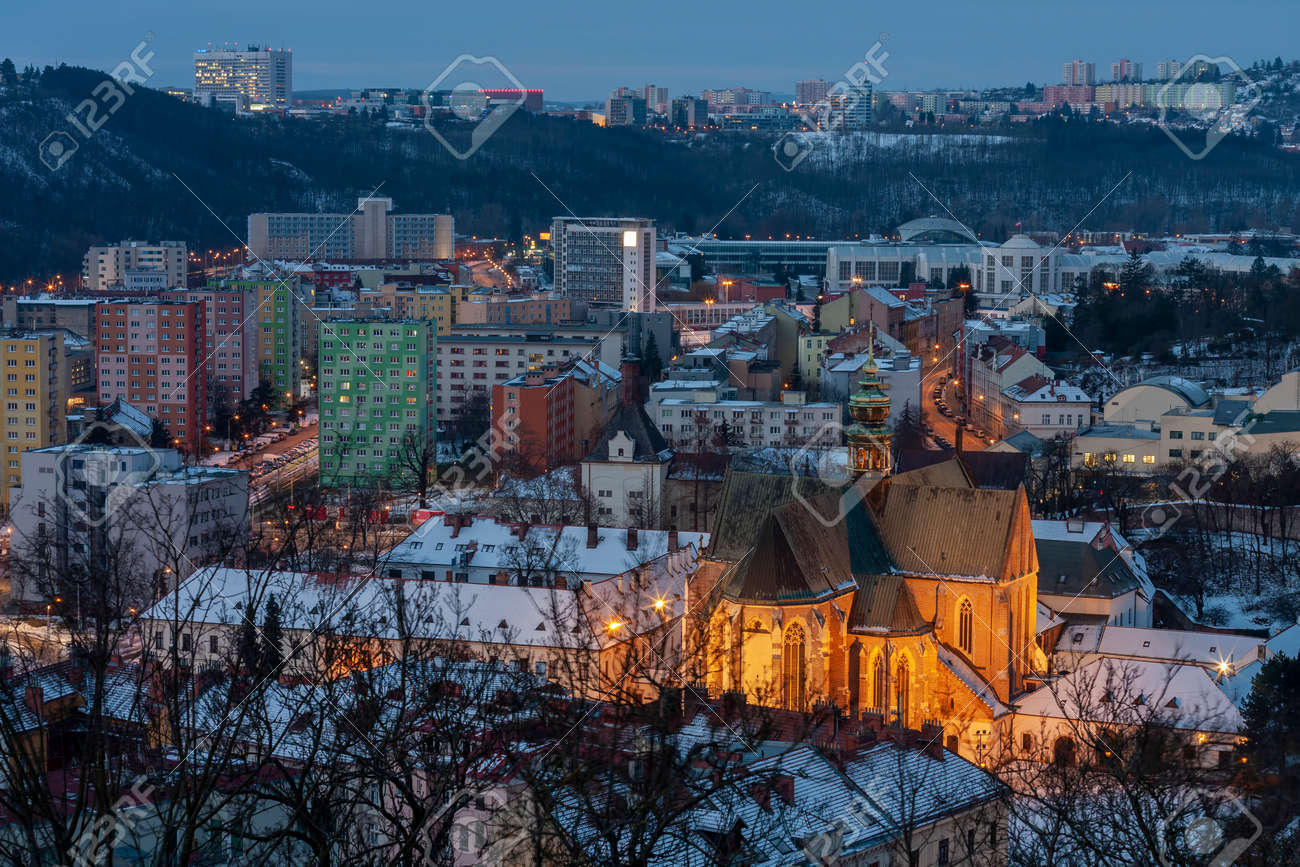 Panoramic view of the Mendel Square with The Basilica of the Assumption of Our Lady in Brno in Czech Republic. Winter sunrise time. On background under the hill Brno Exhibition center. - 163052066