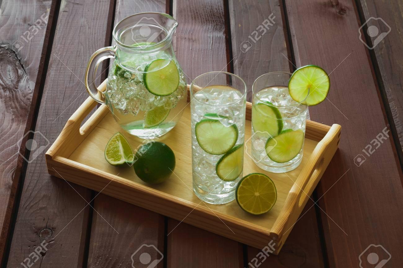 Vassoi In Legno Con Vetro : Due bevande acqua con calce sul vassoio in legno con ghiaccio e la