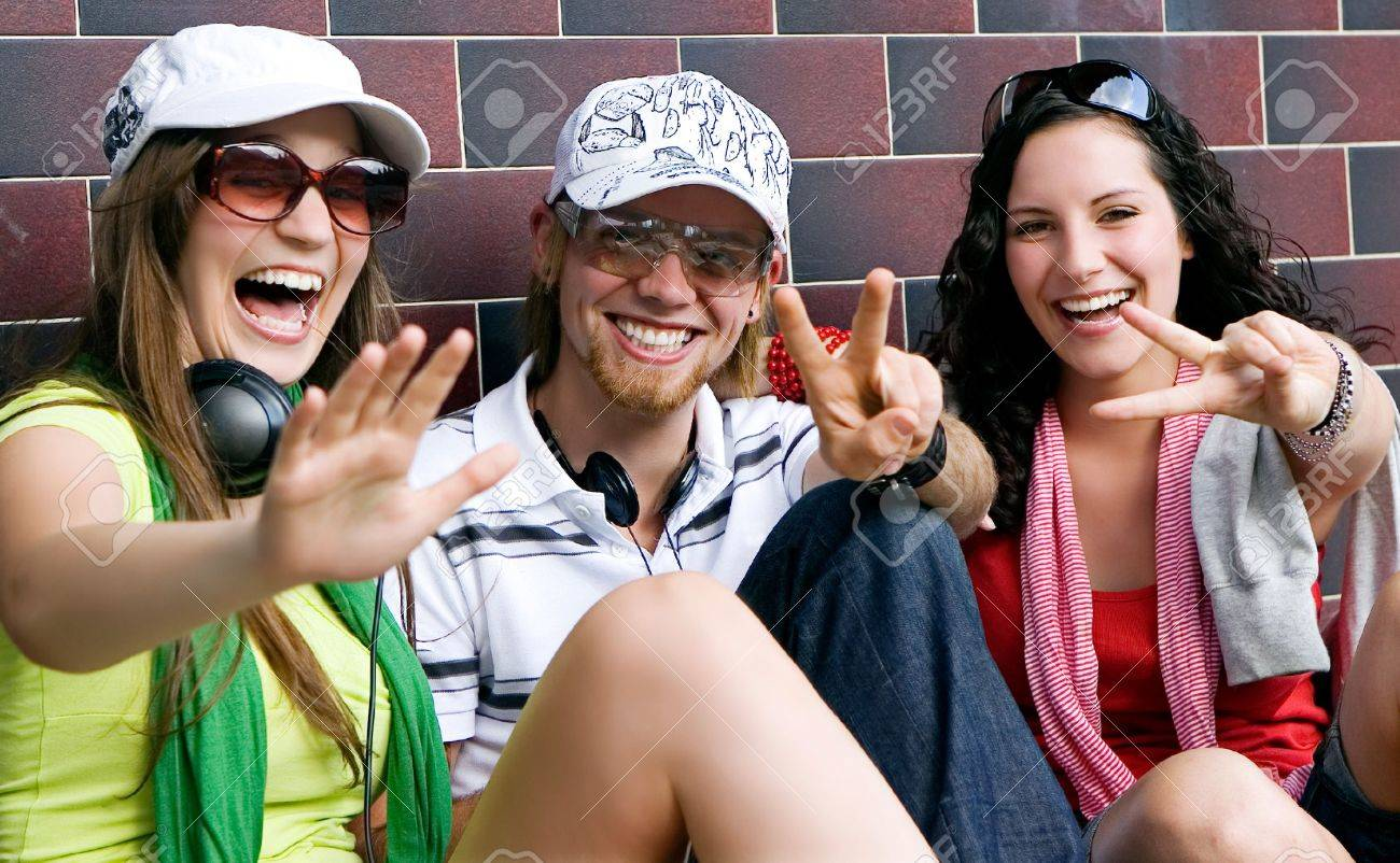 students are sitting beside a wall and making a rest Stock Photo - 5437842