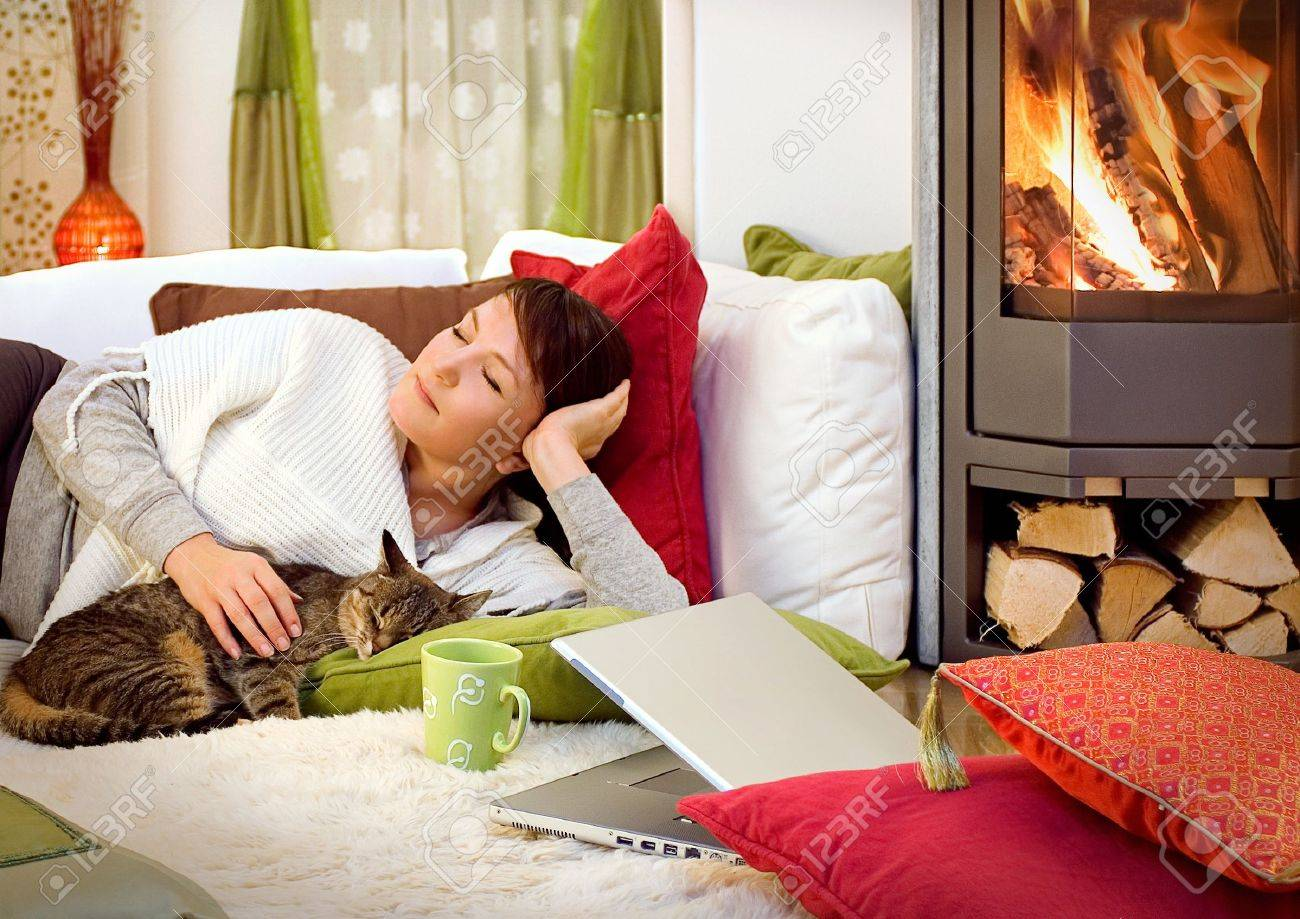 woman with a little cat relaxing in front of a fireplace Stock Photo - 5512256