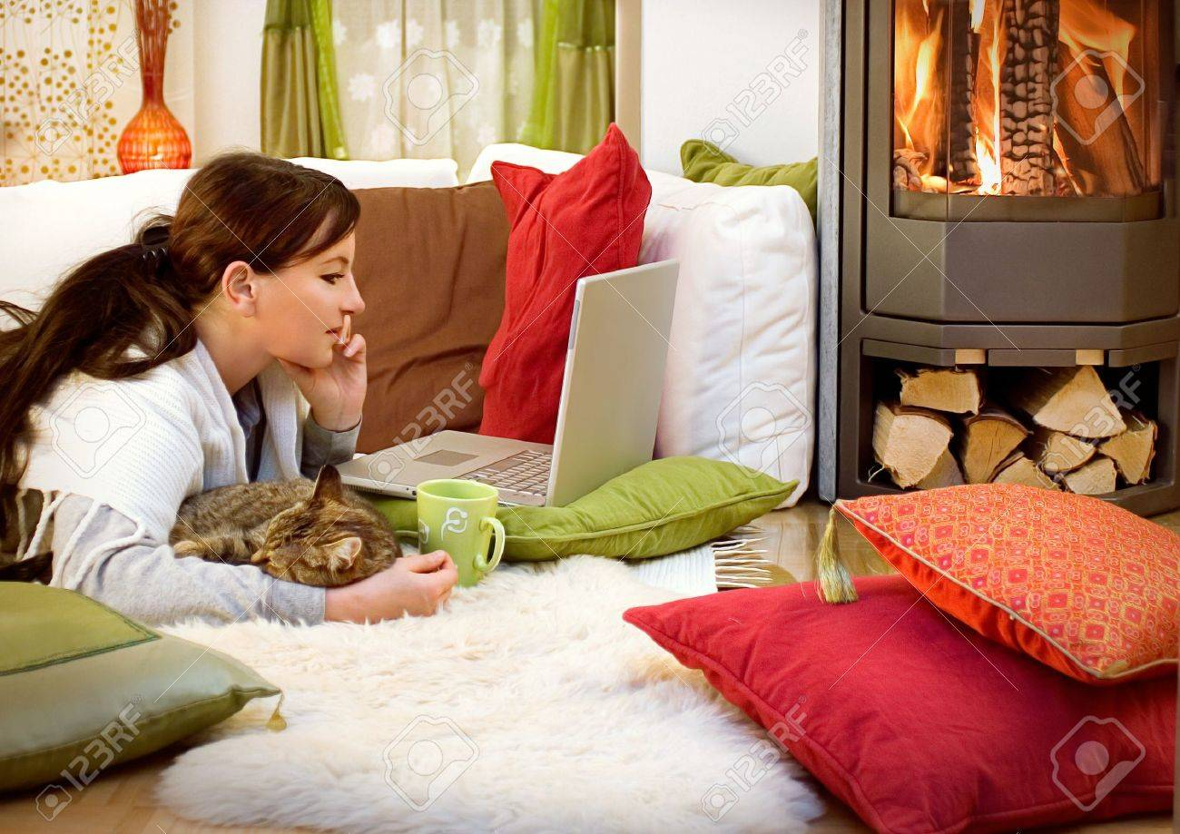 woman with a little cat relaxing in front of a fireplace stock