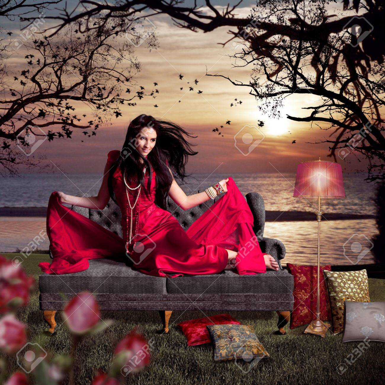 beautiful woman sitting on an old sofa beside a lake Stock Photo - 15385397