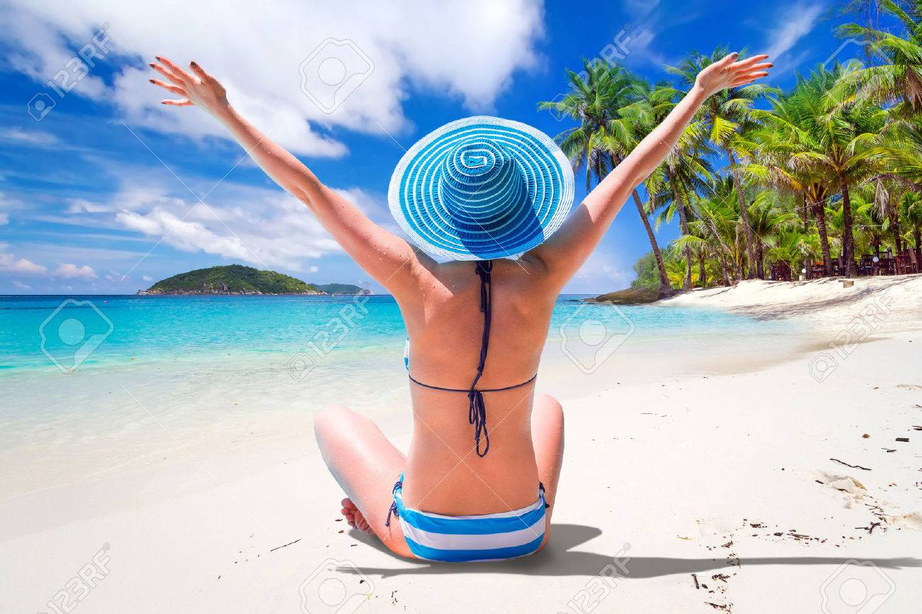 Woman in hat enjoying sun holidays on the tropical beach Stock Photo - 53176188