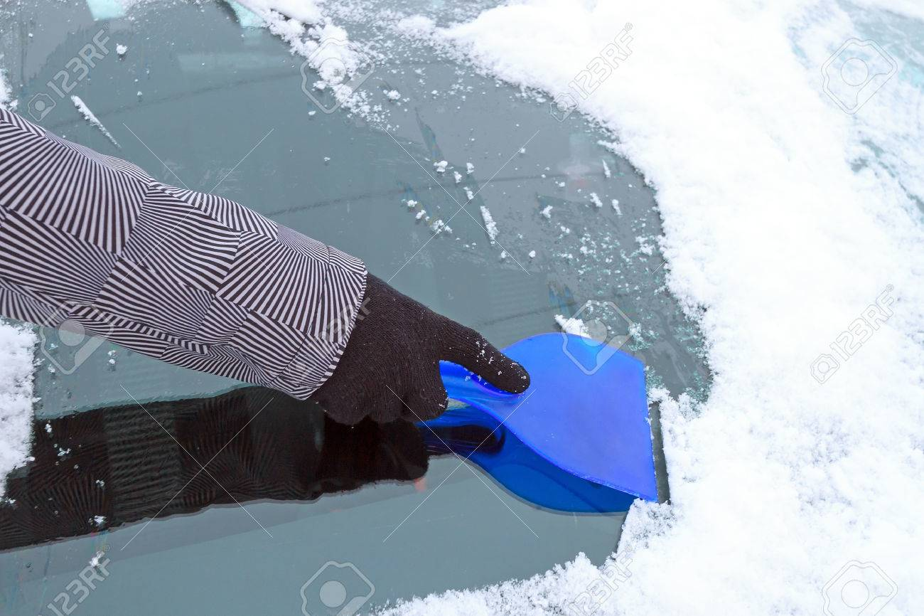 Hand scraping ice from the car window during winter time Stock Photo - 59421212