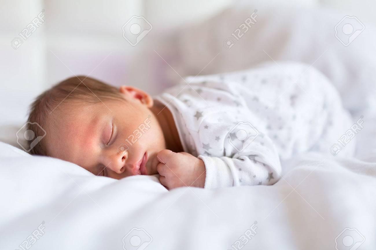 Newborn baby boy sleeping in bed - 55970034