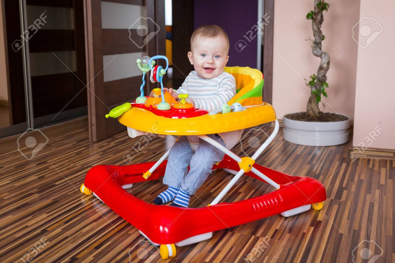 First steps of the boy in a baby walker - 55970031