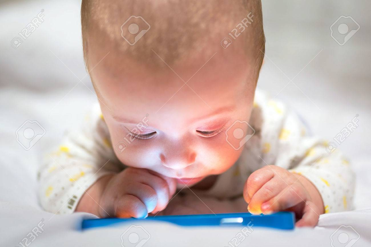 Baby boy watching movie on the mobile phone Stock Photo - 55970429