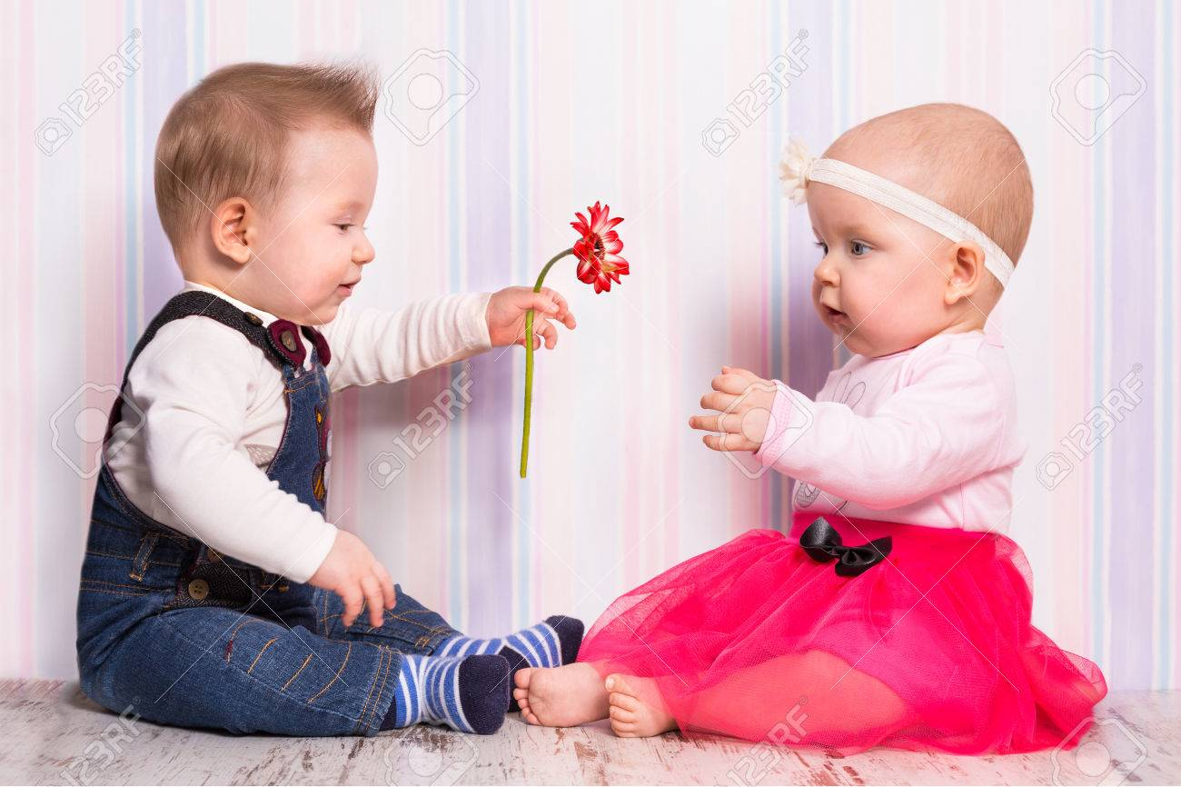Baby Boy Giving A Flower To Baby Girl On Valentines Day Stock Photo