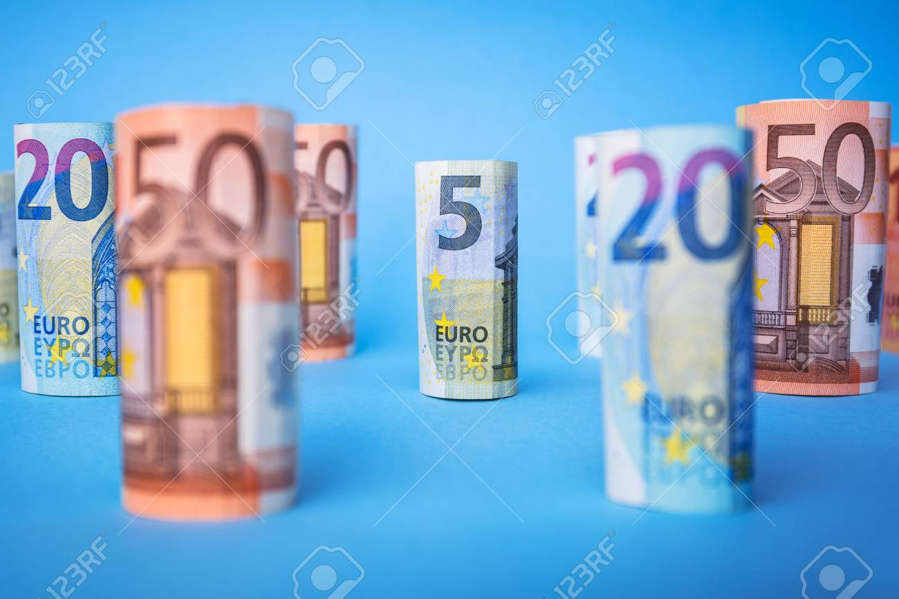 Rolled up euro banknotes on blue background Stock Photo - 75145705