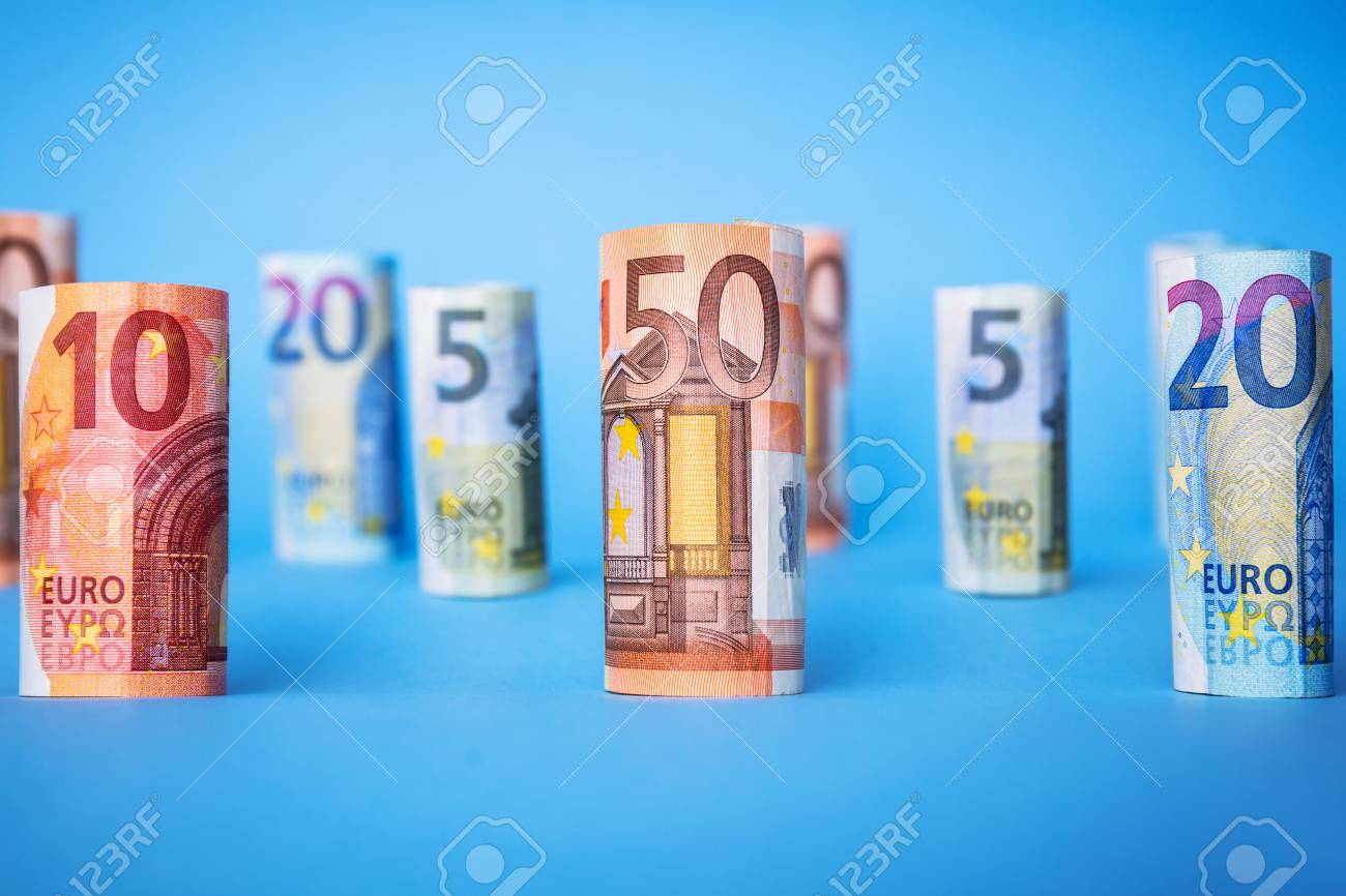 Rolled up euro banknotes on blue background Stock Photo - 75164560