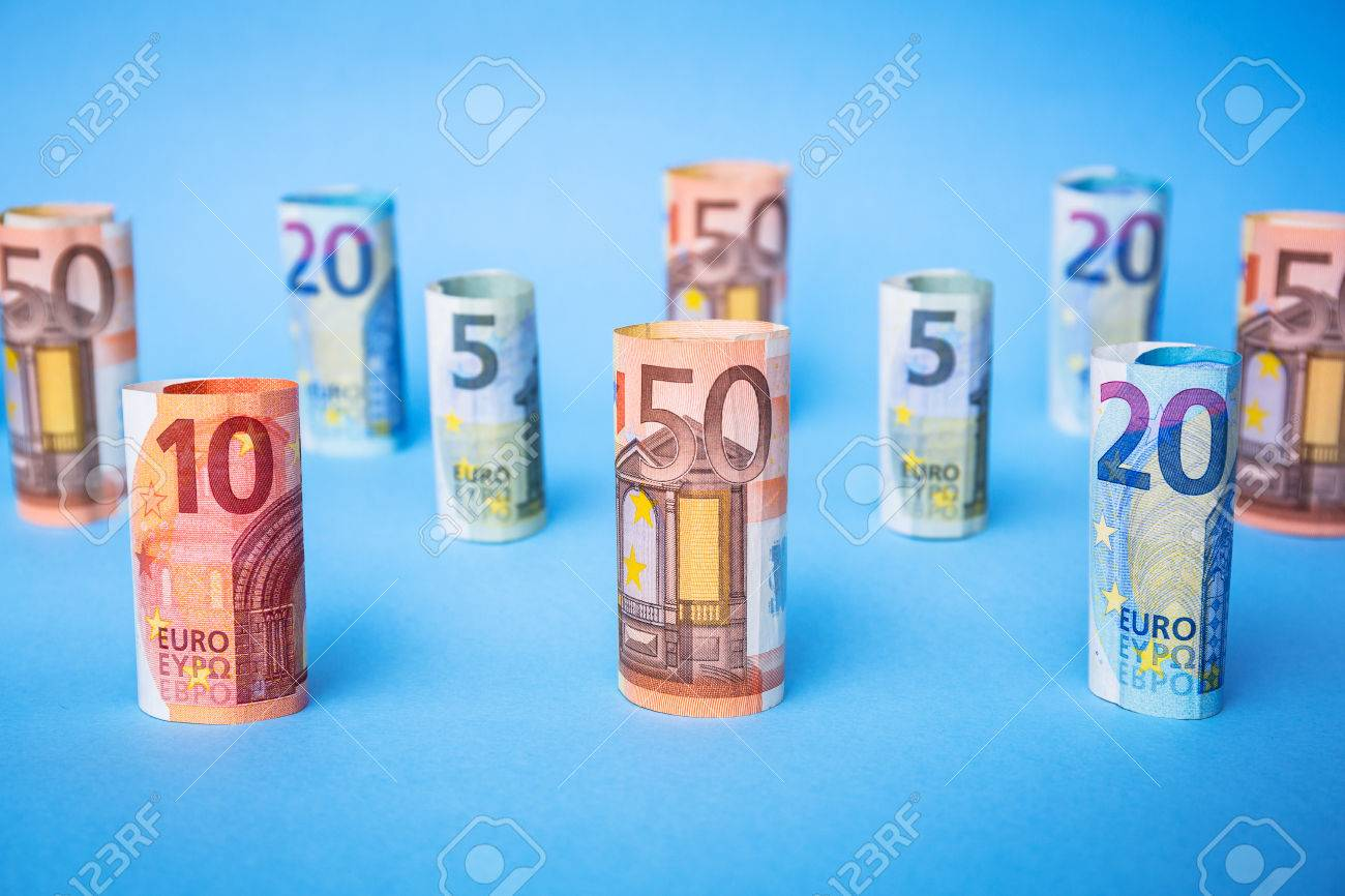 Rolled up euro banknotes on blue background Stock Photo - 75207217