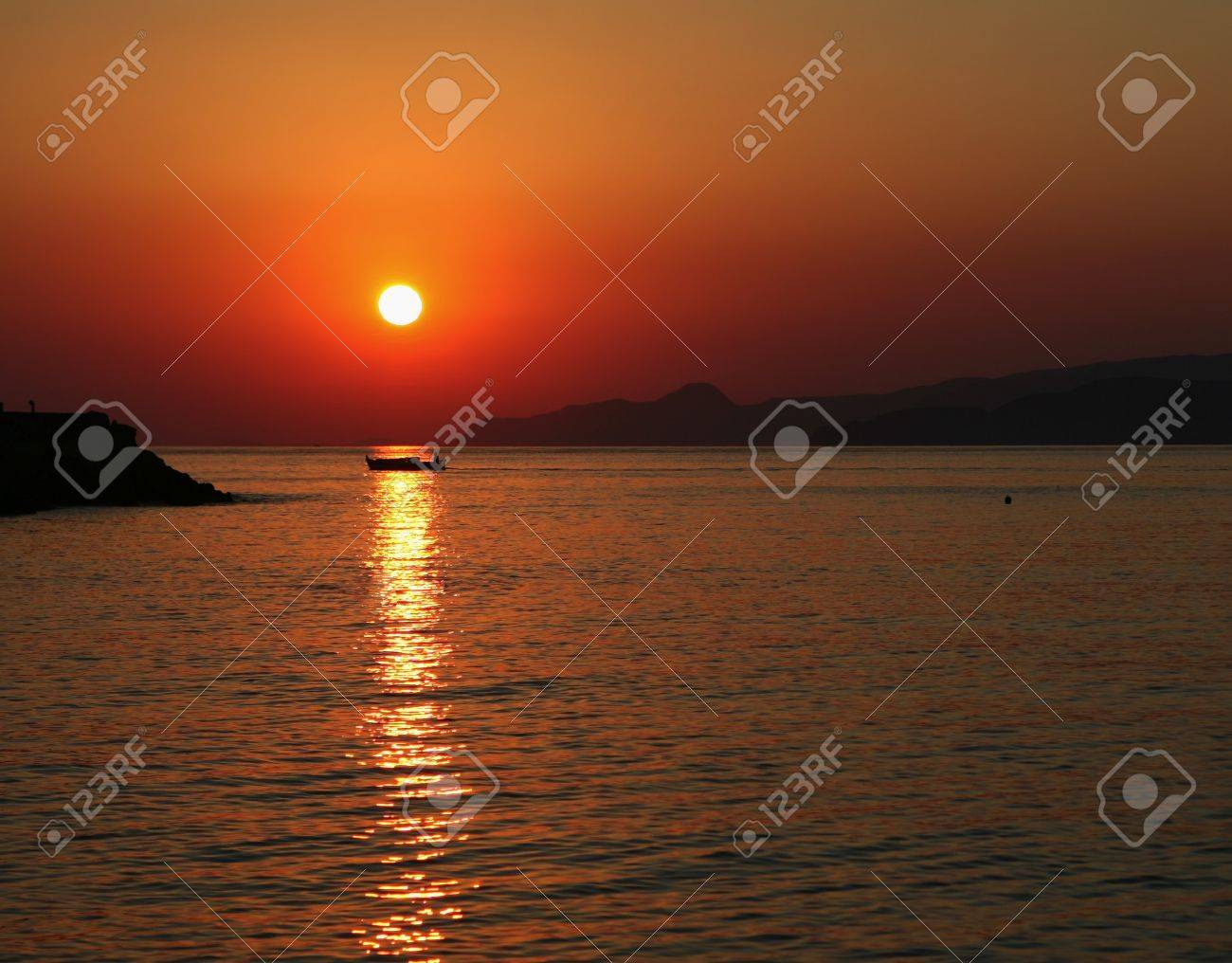 The sun rises over the hills beyond Agios Nikolaos on Crete, Greece, while a lone fisherman makes his way back to harbour with the night's catch. Stock Photo - 7533430