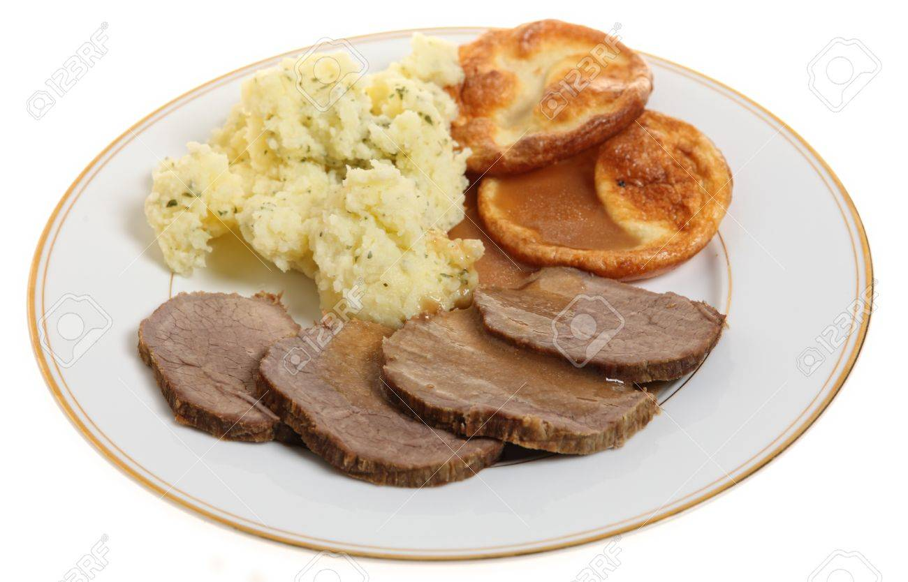 A traditional British meal of roast beef silverside with Yorkshire puddings (popovers) and mashed parsley potatoes. Stock Photo - 9146716