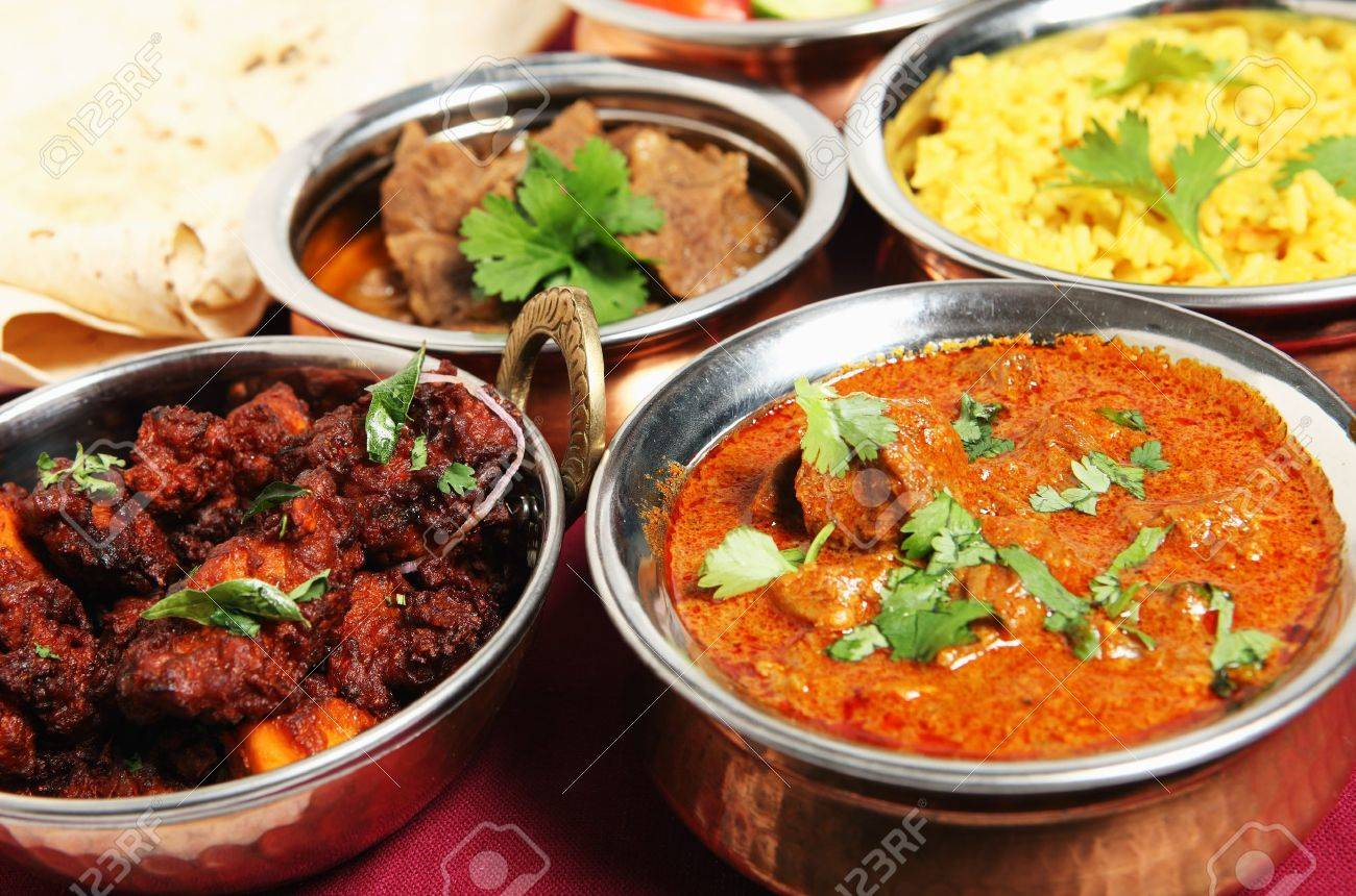Chicken fry (left) and Kashmiri lamb curry (right) in front of chapattis, beef korma and saffron rice. Stock Photo - 9232385
