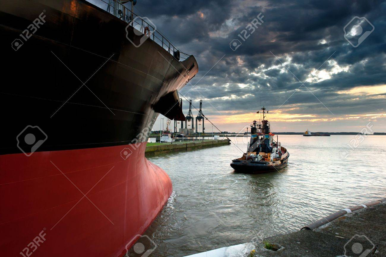 Tug boat taking out the ship from the harbor Stock Photo - 8518549