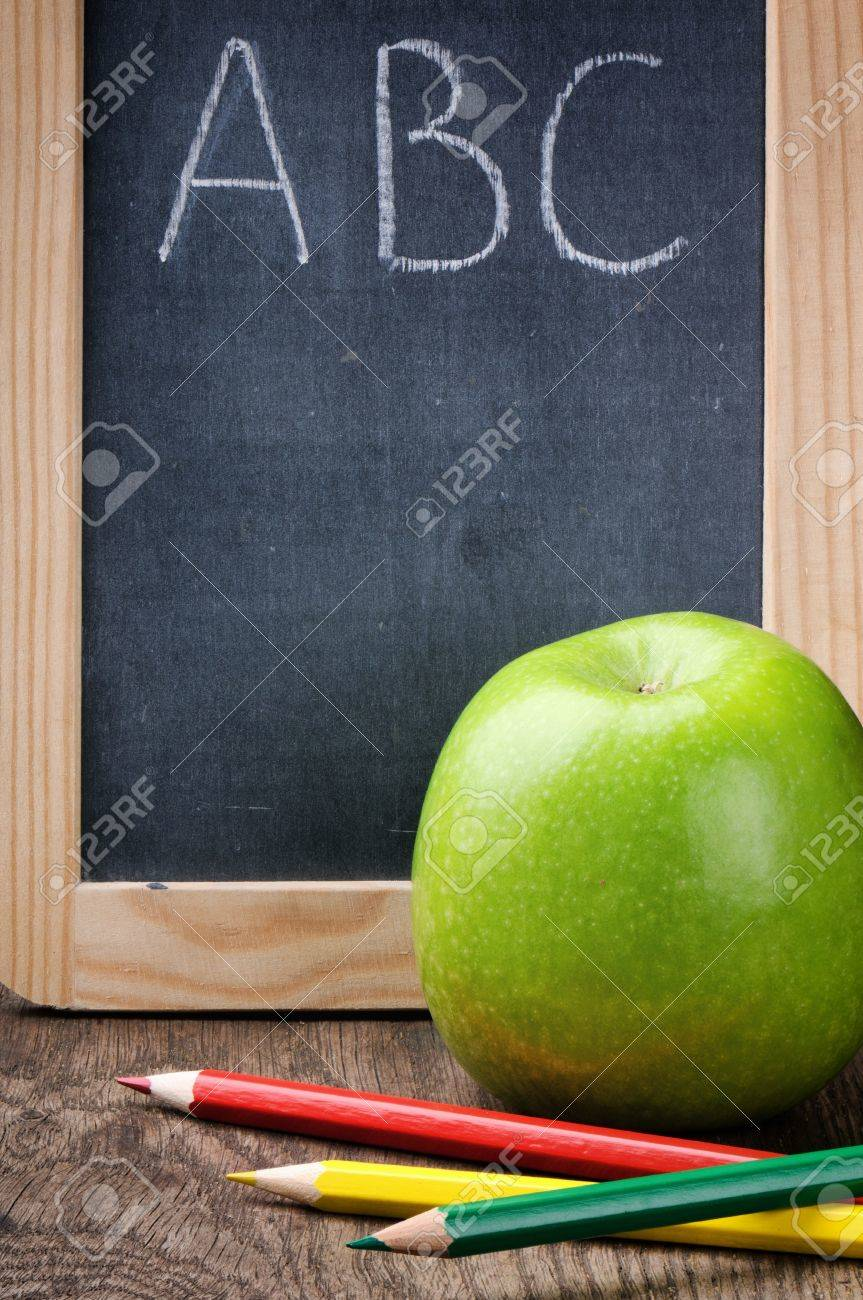 Colorful crayons and apple on wooden desk Stock Photo - 14931286