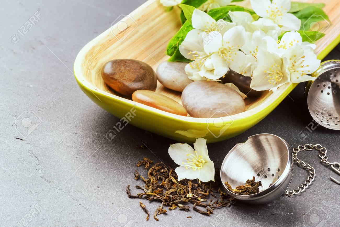 Tea Infuser With Dry Green Tea Leaves And Fresh Jasmine Flowers