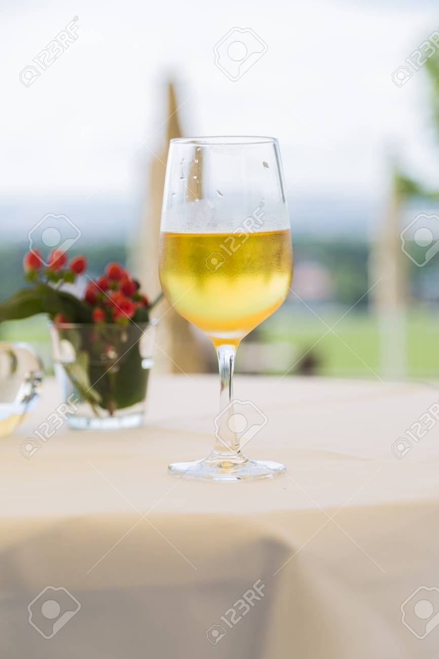 One shiny clean wineglass with white wine near red flowers on one shiny clean wineglass with white wine near red flowers on table with white tablecloth on mightylinksfo
