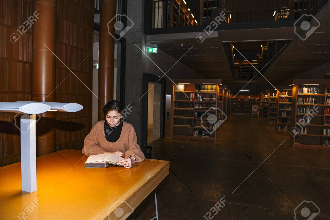 Girl reads book by light of lamp sitting at table - 132001829