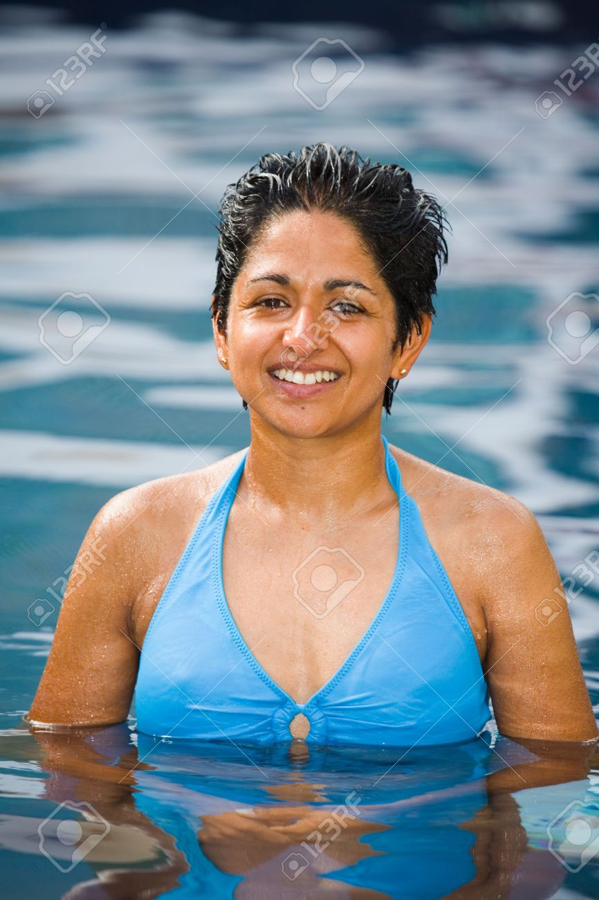 An athletic looking Indian woman in blue bikini stands smiling in a swimming pool Stock Photo - 5066220