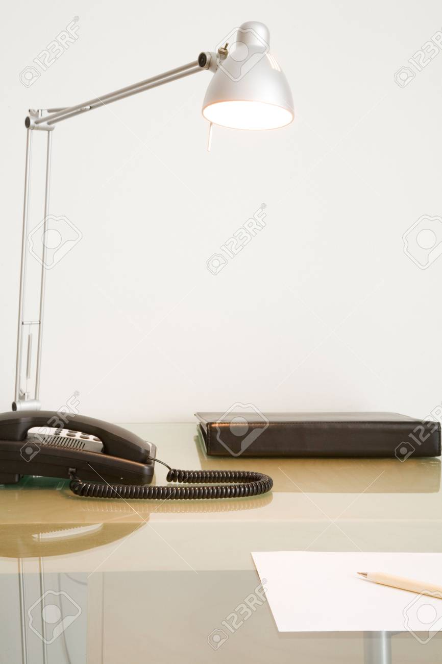 Cropped office desk with phone, lamp and note pad against white wall. Stock Photo - 5531606