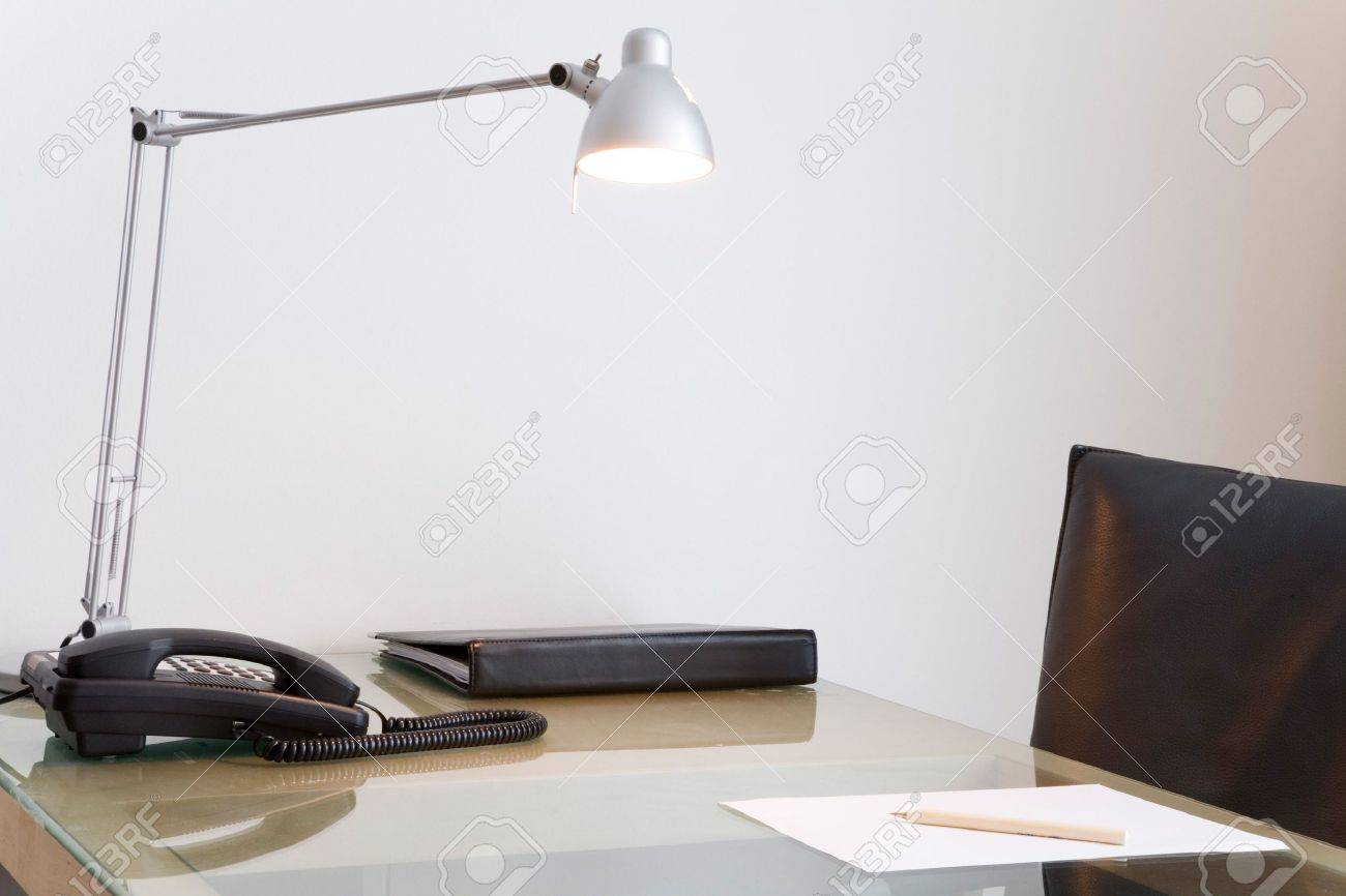 Desk with lamp and black leather swivel chair. White wall in the background. Stock Photo - 5558978