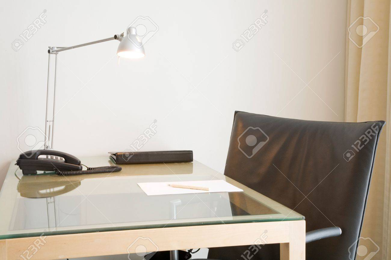 Desk with lamp and black leather swivel chair. Could depict an office desk, home study or hotel room. Stock Photo - 6125422