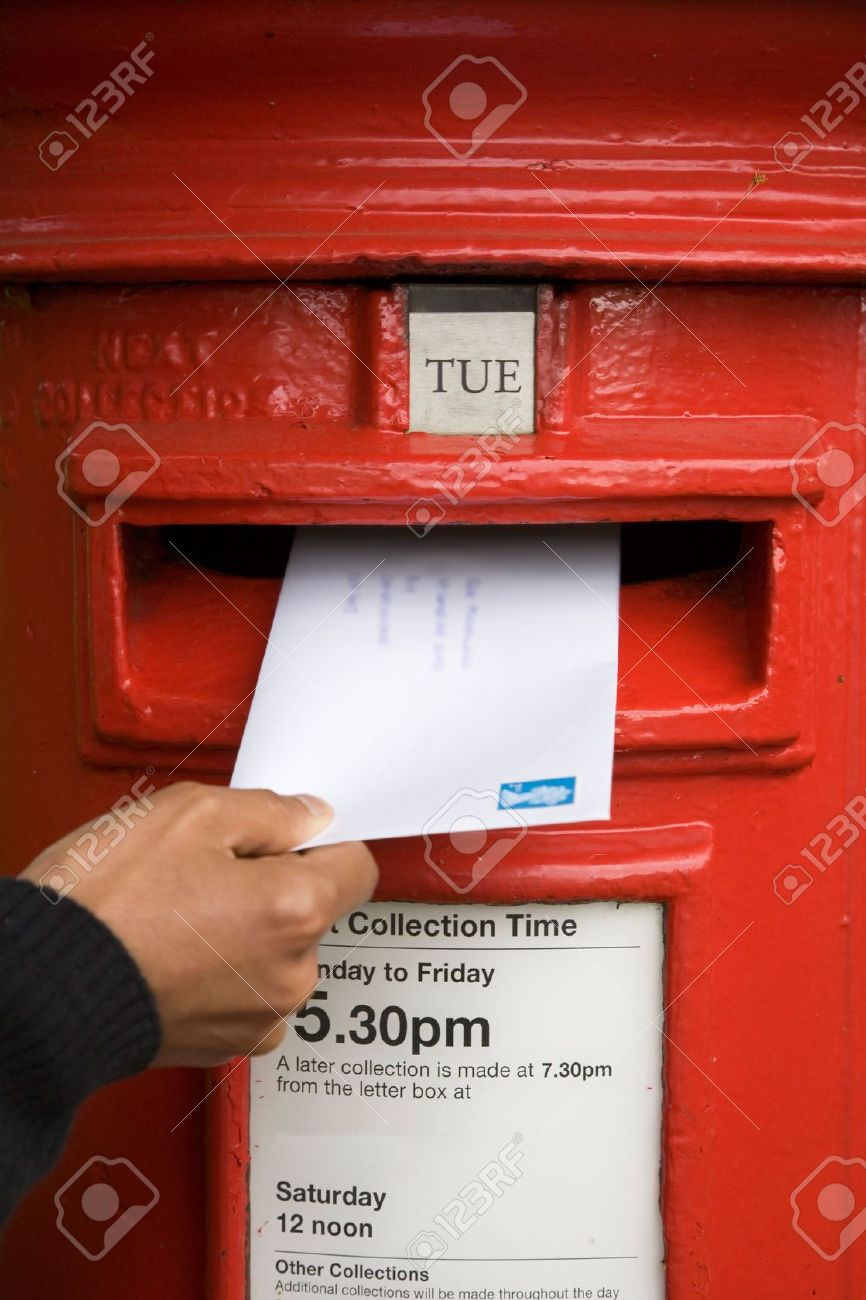 A woman posts a letter in a traditional British red post box Stock Photo - 6177384