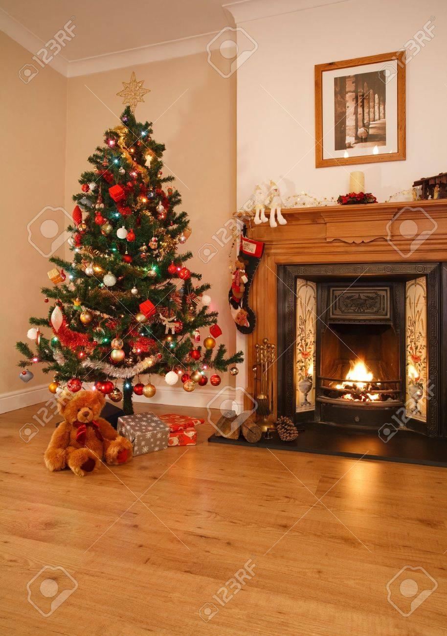 Woonkamer met kerst decoraties, een open haard en de kerst boom ...