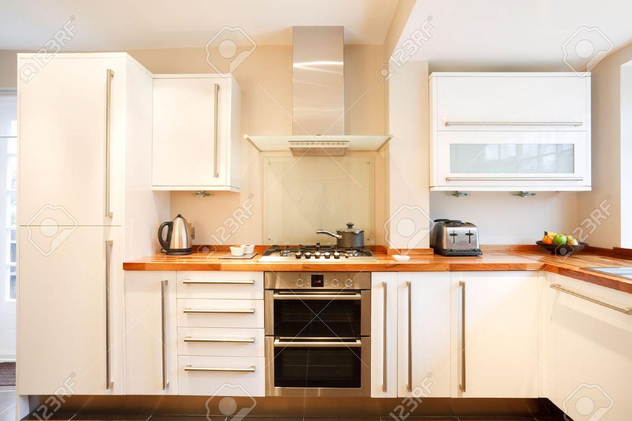 moderna cocina blanco con encimera de madera y de acero inoxidable foto de archivo