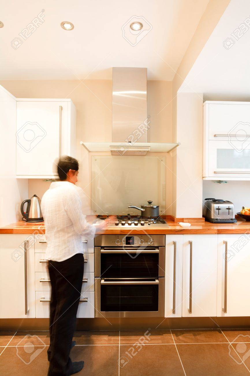 Indian Asian woman in a stylish modern kitchen with white units and a wooden worktop Stock Photo - 9027497